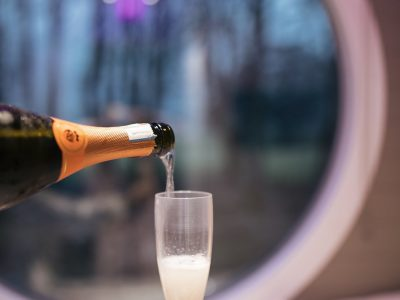 Woman pours glass of champagne in hot tub lodge Glencoe, Scotland