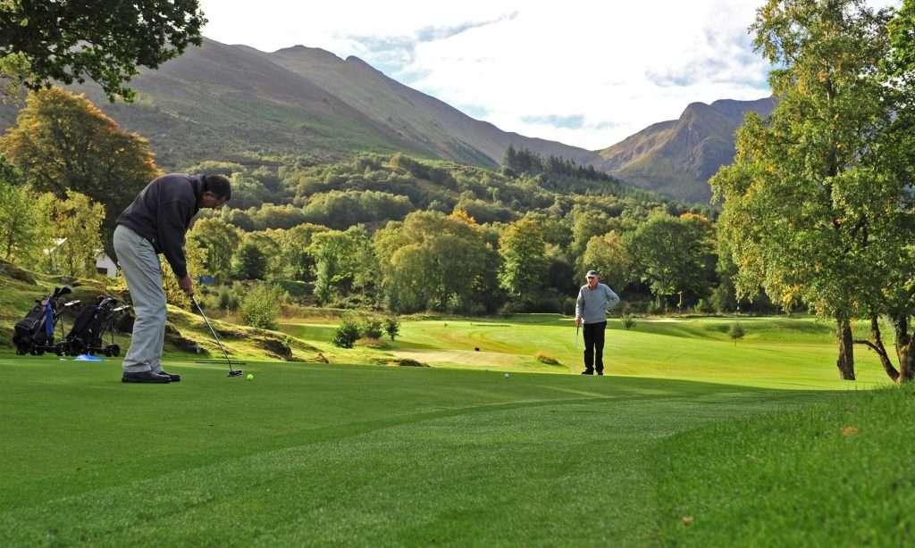 Golfers playing golf at Woodlands Glencoe, Scotland.