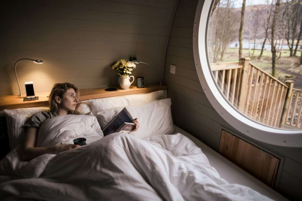 Woman reading book in RiverBeds luxury wee lodge with hot tub in Glencoe, Scotland